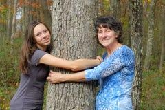 Mujer y muchacha que abrazan el árbol Foto de archivo