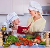 Mujer y muchacha que cocinan los veggies Imágenes de archivo libres de regalías
