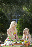 Mujer y muchacha que cultivan un huerto plantando las flores Imagenes de archivo