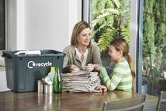 Mujer y muchacha que preparan el papel usado para reciclar Fotos de archivo libres de regalías