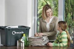 Mujer y muchacha que preparan el papel usado para reciclar Fotos de archivo