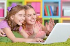 Mujer y muchachas que usan el ordenador portátil Imagenes de archivo