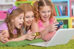 Mujer y muchachas que usan el ordenador portátil Fotografía de archivo