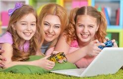 Mujer y muchachas que usan el ordenador portátil Foto de archivo