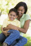 Mujer y muchacho joven al aire libre que abrazan y que sonríen Imagenes de archivo