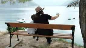 Mujer y muchacho que se sientan haciendo frente al mar que toma imágenes en el teléfono metrajes