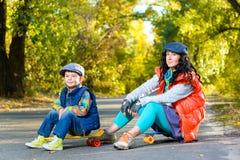 Mujer y muchacho sonrientes que se sientan en el plástico del color Fotografía de archivo libre de regalías