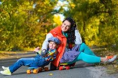 Mujer y muchacho sonrientes que se sientan en el plástico del color Foto de archivo
