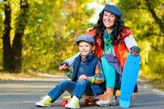 Mujer y muchacho sonrientes que se sientan en el plástico del color Fotos de archivo