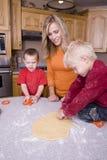 Mujer y muchachos que hacen las galletas Foto de archivo libre de regalías