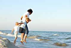 Mujer y muchachos que saltan ondas Fotografía de archivo