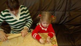 Mujer y niña pequeña que preparan el pan de jengibre para la cena de la Nochebuena de la familia almacen de metraje de vídeo