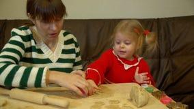 Mujer y niña pequeña que preparan el pan de jengibre para la cena de la Nochebuena de la familia almacen de video