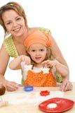 Mujer y niña que hacen las galletas Fotos de archivo libres de regalías