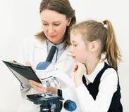 Mujer y niña que usa el microscopio Fotografía de archivo