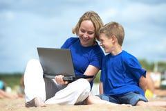 Mujer y niño con el ordenador en la playa imagenes de archivo