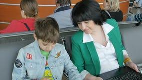 Mujer y niño en el aeropuerto que espera el avión metrajes