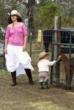 Mujer y niño en la granja que acaricia Imágenes de archivo libres de regalías