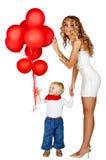 Mujer y niño pequeño con los globos rojos Fotografía de archivo libre de regalías