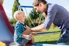 Mujer y niño pequeño que canalizan abajo de diapositiva en el patio Imagen de archivo libre de regalías