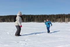 Mujer y niño pequeño que juegan bolas de nieve en el riverbank imágenes de archivo libres de regalías
