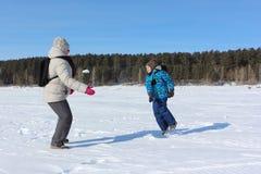 Mujer y niño pequeño que juegan bolas de nieve en riverbank en el invierno foto de archivo
