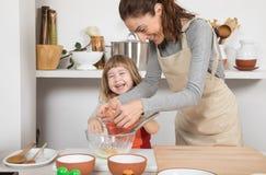 Mujer y niño que cocinan con la risa del huevo Foto de archivo libre de regalías