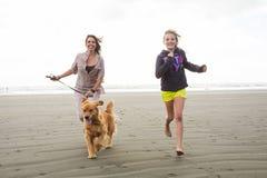 Mujer y niño que corren con un perro Fotos de archivo libres de regalías