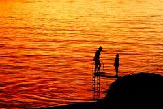 Mujer y niño que se bañan en la puesta del sol Fotografía de archivo libre de regalías