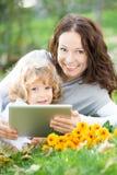 Mujer y niño que usa la PC de la tablilla al aire libre Fotografía de archivo
