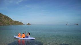 Mujer y niños canoeing en la playa metrajes