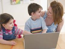 Mujer y niños con el ordenador portátil que se sienta en la tabla Imagenes de archivo