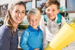 Mujer y niños en el día de la inscripción con los conos de la escuela imágenes de archivo libres de regalías