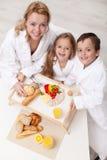 Mujer y niños que comen una luz y un bocado sano Imagen de archivo
