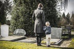 Mujer y niño en el cementerio Imagen de archivo libre de regalías