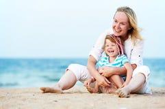 Mujer y niño en la playa del mar Fotos de archivo