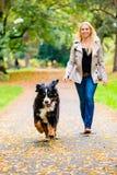 Mujer y perro en el recuperación del juego del palillo fotos de archivo