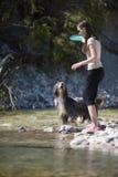 Mujer y perro que caminan en agua fotografía de archivo libre de regalías