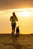 Mujer y perro que corren en puesta del sol Foto de archivo libre de regalías