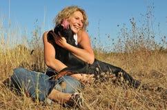 Mujer y perro sonrientes Fotos de archivo libres de regalías