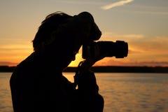Mujer y puesta del sol del fotógrafo sobre el lago Imagenes de archivo
