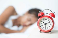 Mujer y reloj de alarma durmientes jovenes Fotos de archivo libres de regalías