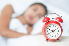 Mujer y reloj de alarma durmientes jovenes Imágenes de archivo libres de regalías