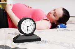 Mujer y reloj de mentira embarazados Fotos de archivo