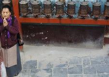 Mujer y ruedas de rezo budistas Fotos de archivo libres de regalías