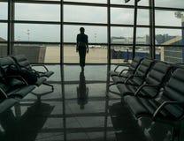 Mujer y sillas para los pasajeros en aeropuerto Imagen de archivo