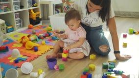 Mujer y su bebé que juegan con los cubos de madera almacen de metraje de vídeo