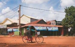 Mujer y su bici en Camboya rural foto de archivo libre de regalías