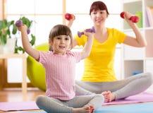 Mujer y su hija del niño que hacen ejercicios de la aptitud con pesas de gimnasia Fotografía de archivo