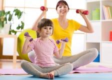 Mujer y su hija del niño que hacen ejercicios de la aptitud con pesas de gimnasia Fotos de archivo